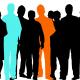 Stående människor, de flesta svarta men några i färg. Illustration.